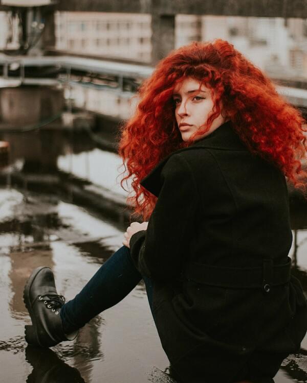 Mulher sentada, olhando para trás, com um cabelo vermelho e cacheado.