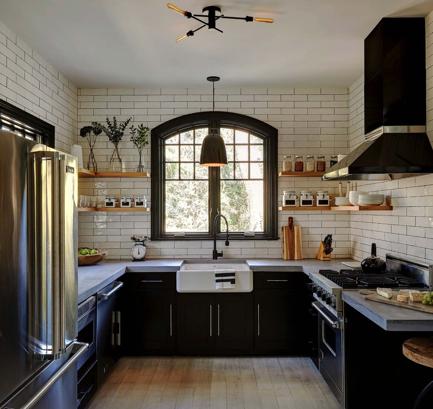 Modern industrial farmhouse kitchen with black cabinets, silver hardware, white subway tile backsplash and open shelving with cement countertops