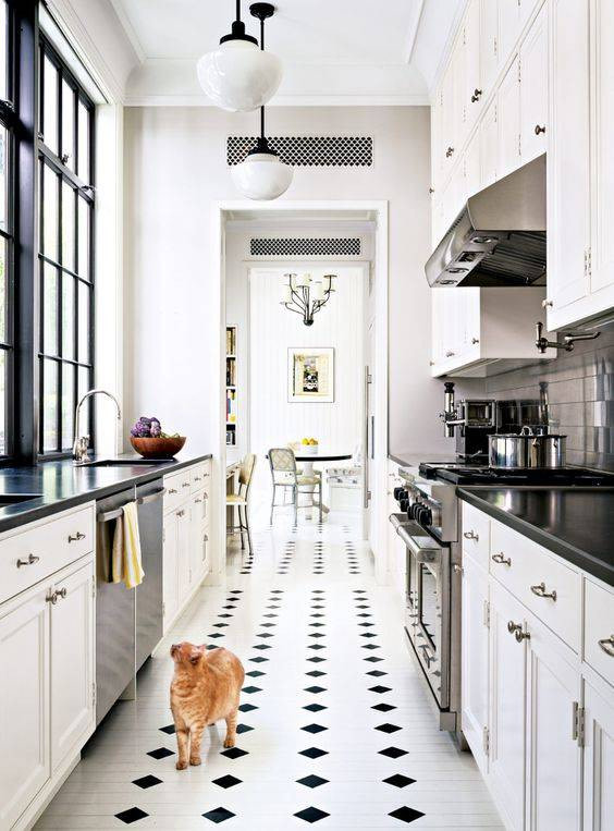 traditional galley kitchen with black and white finishes. white cabinets are complemented by stark black countertops and a black and white tile floor