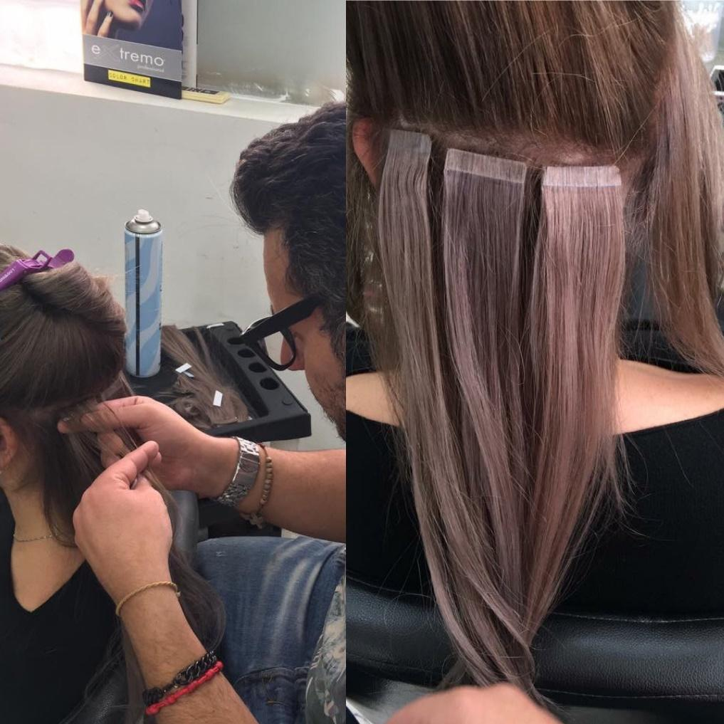 hair stylist placing tape in hair extensions in Houston