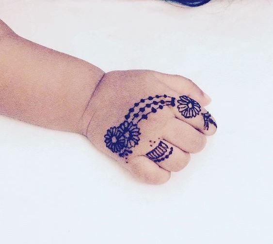 Little cute hand of a baby  girl showing her mehndi design