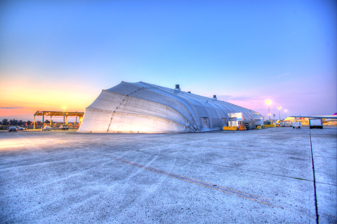 Transportation project tension fabric structure for aviation on an airport runway at dawn.