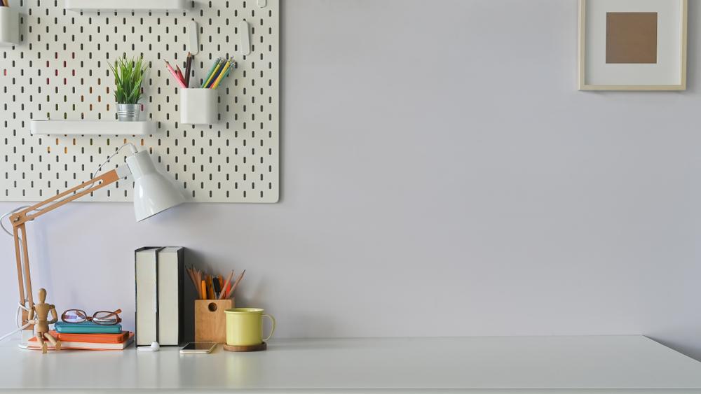 Um cantinho de home office com uma luminária.
