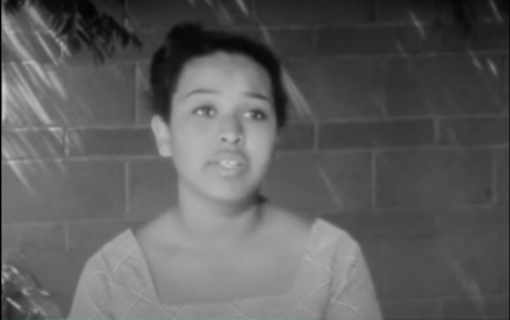 Felicia (1965). A black-and-white close up of Felicia, a 16-year-old Black girl from Watts, LA, talking to the camera, standing against a brick wall. She has a diamond-patterned top on, and her hair tied up in a bun.