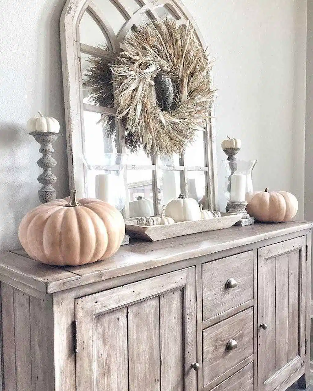 distressed farmhouse hutch with fall wreath, candle holders, and assorted pumpkins