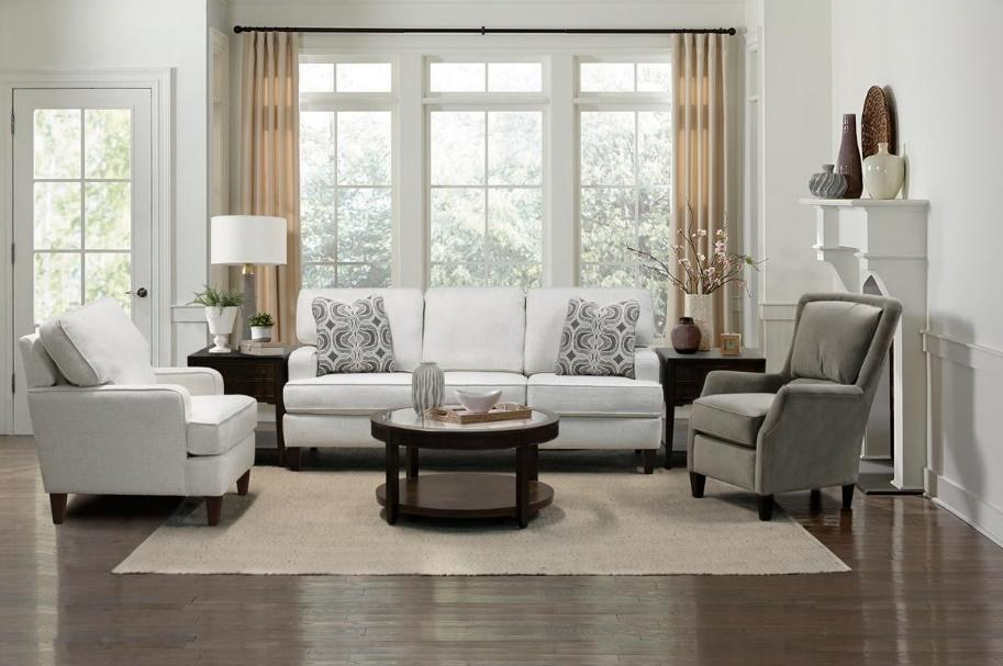 A living room set with a white sofa, a coffee table, and club chairs