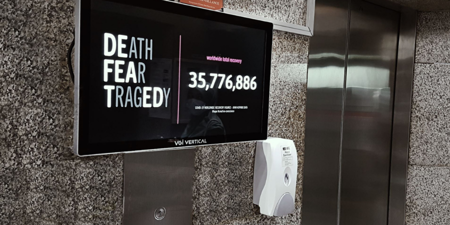 """Digital billboard in a public bathroom with the message """"Death Fear Tragedy (Defeated)"""" and showing the number of people recovered from Covid."""