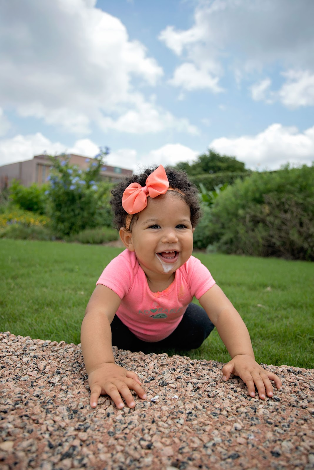 Biracial baby girl playing in the grass.