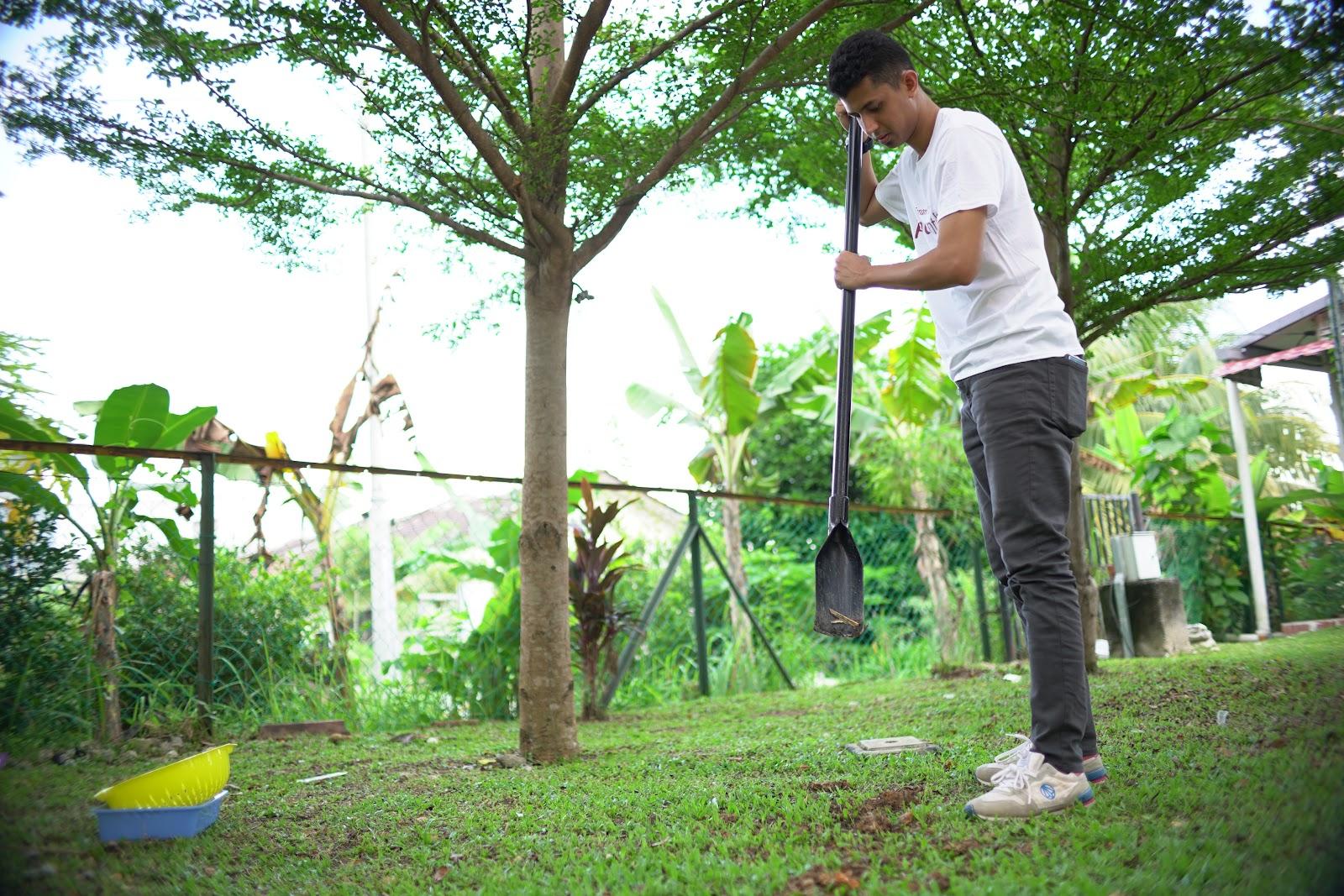Ustaz sedang menggali lubang sedalam 2 kaki untuk menanam uri bayi.
