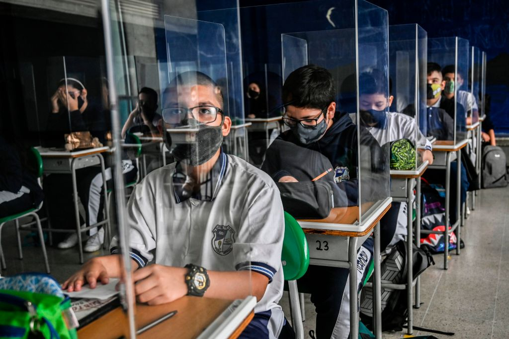 Students take part in a class while partitioned by plexiglass at the Antonio Jose Sucre Public School, amid the COVID 19 pandemic in Itagui, Colombia on February 25, 2021