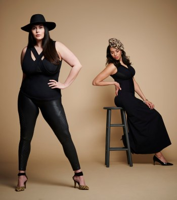 In the foreground one woman wears leather like leggings and a bra free tank top. In the background another woman poses wearing a bra free black dress, while seated on a stool.