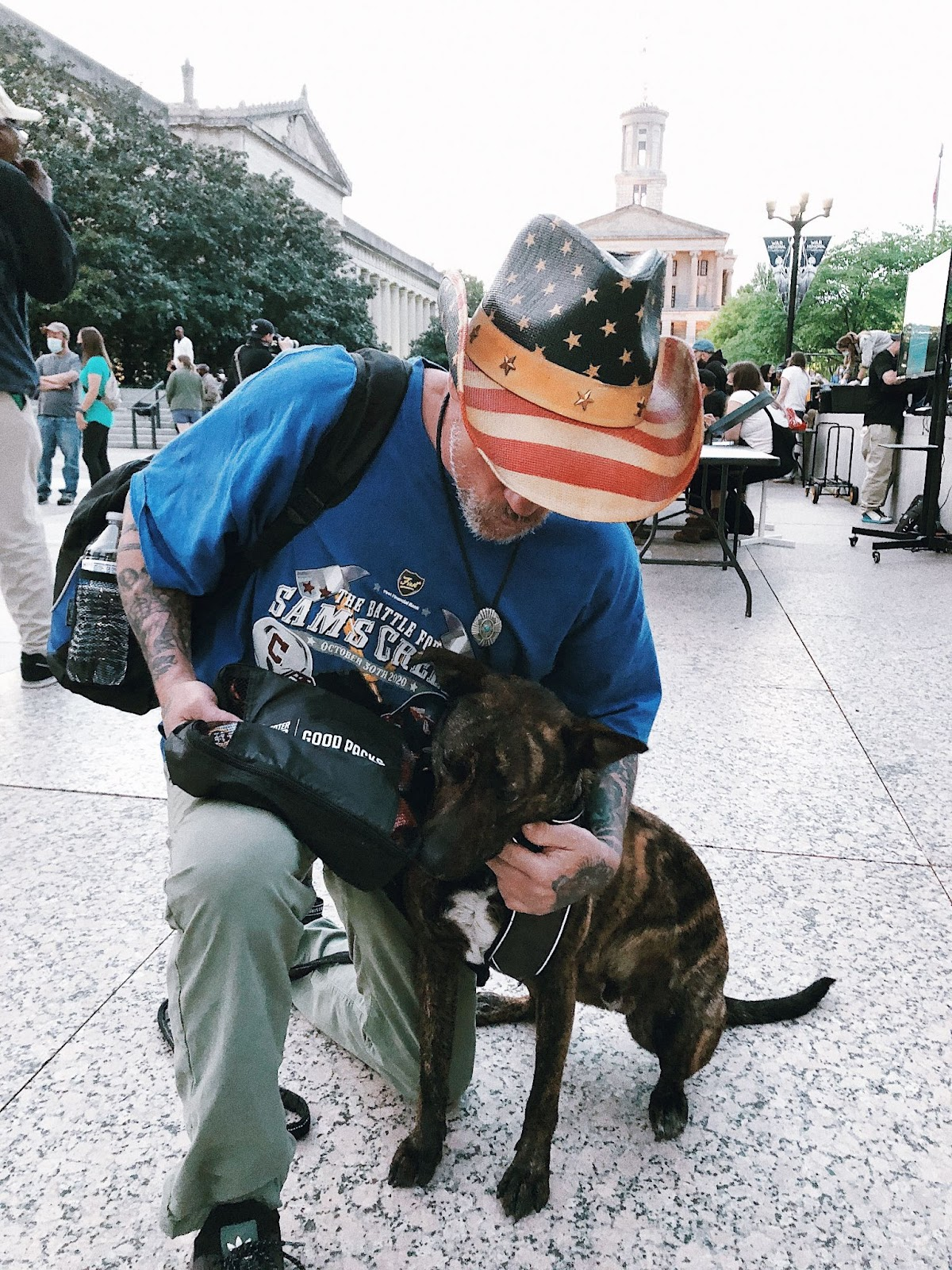Man in American flag hat poses with brown dog and Good Pack at distribution event