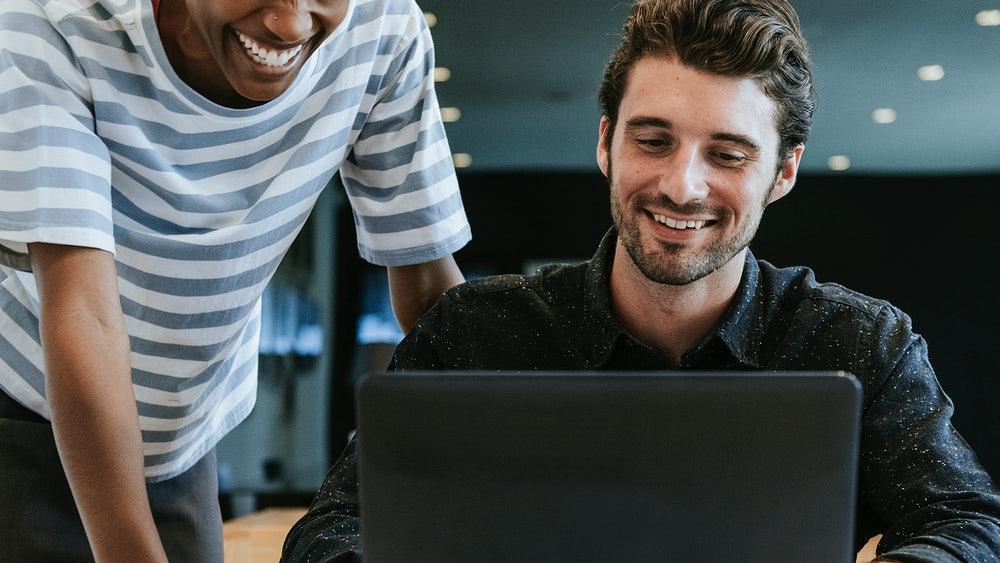 dois homens em frente ao computador -  pair programming