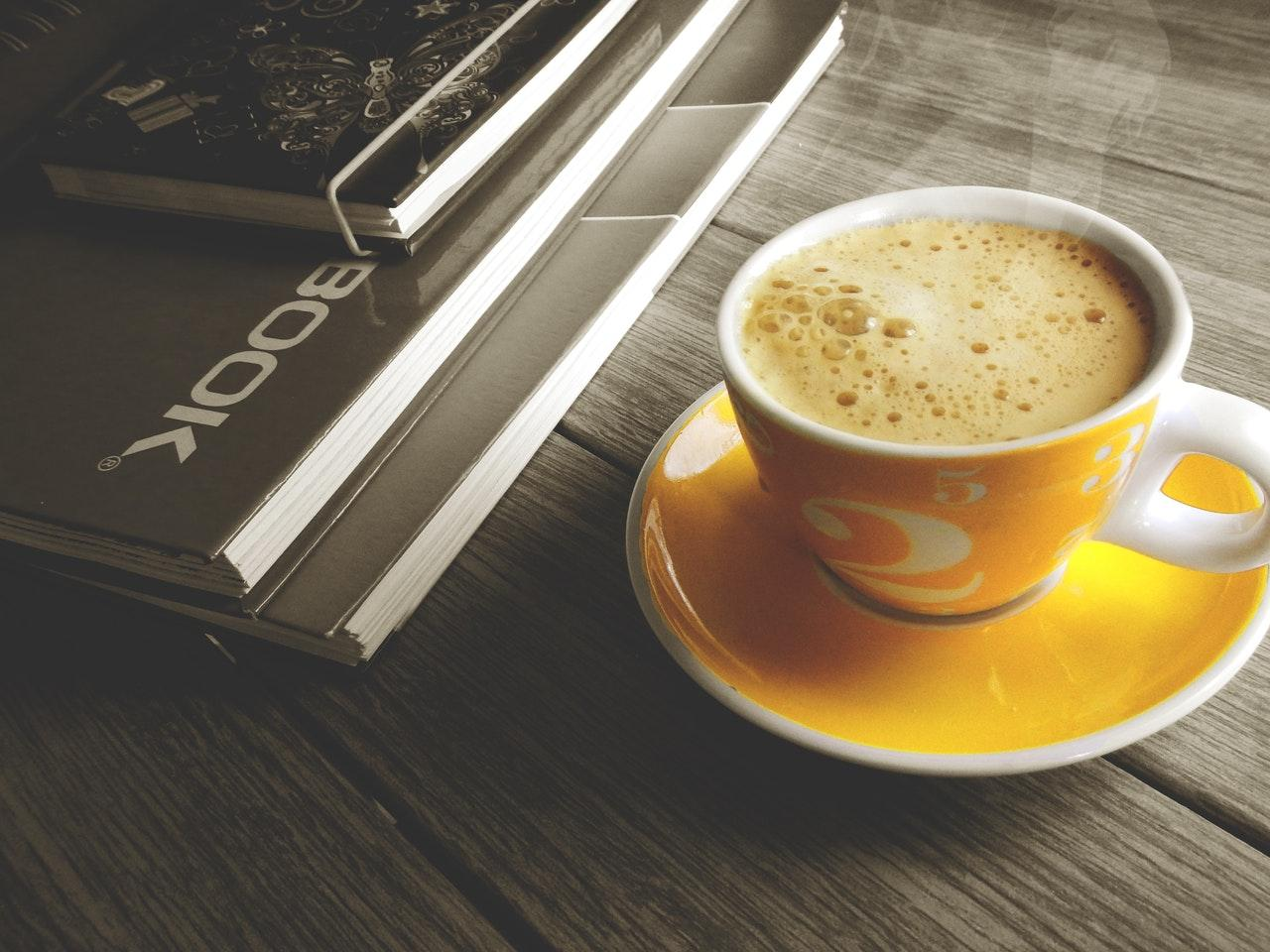 A yellow coffee cup on a wooden desk