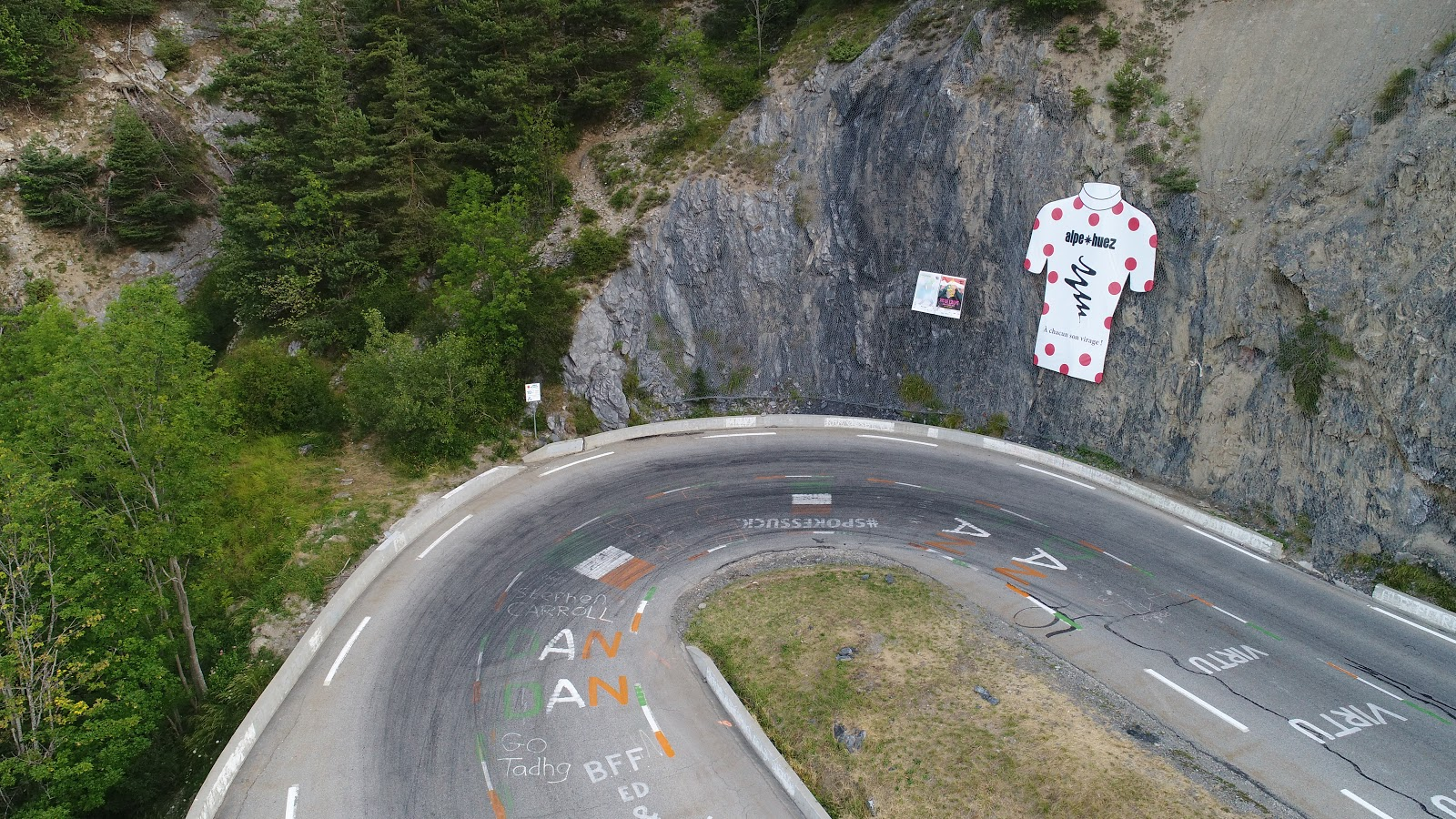Bike climb Alpe d'Huez - turn (tornante) 10 aerial drone photo of mountain stage leader poster on wall and hairpin curve.