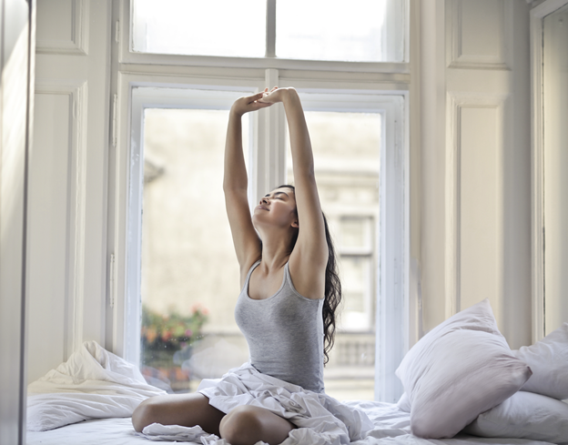 Woman stretches in bed after waking up in the morning.
