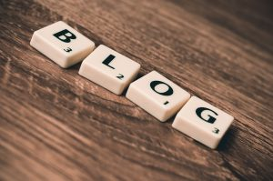 having a blog section on your website is beneficial. there are four cubes on the table and blog is written on them