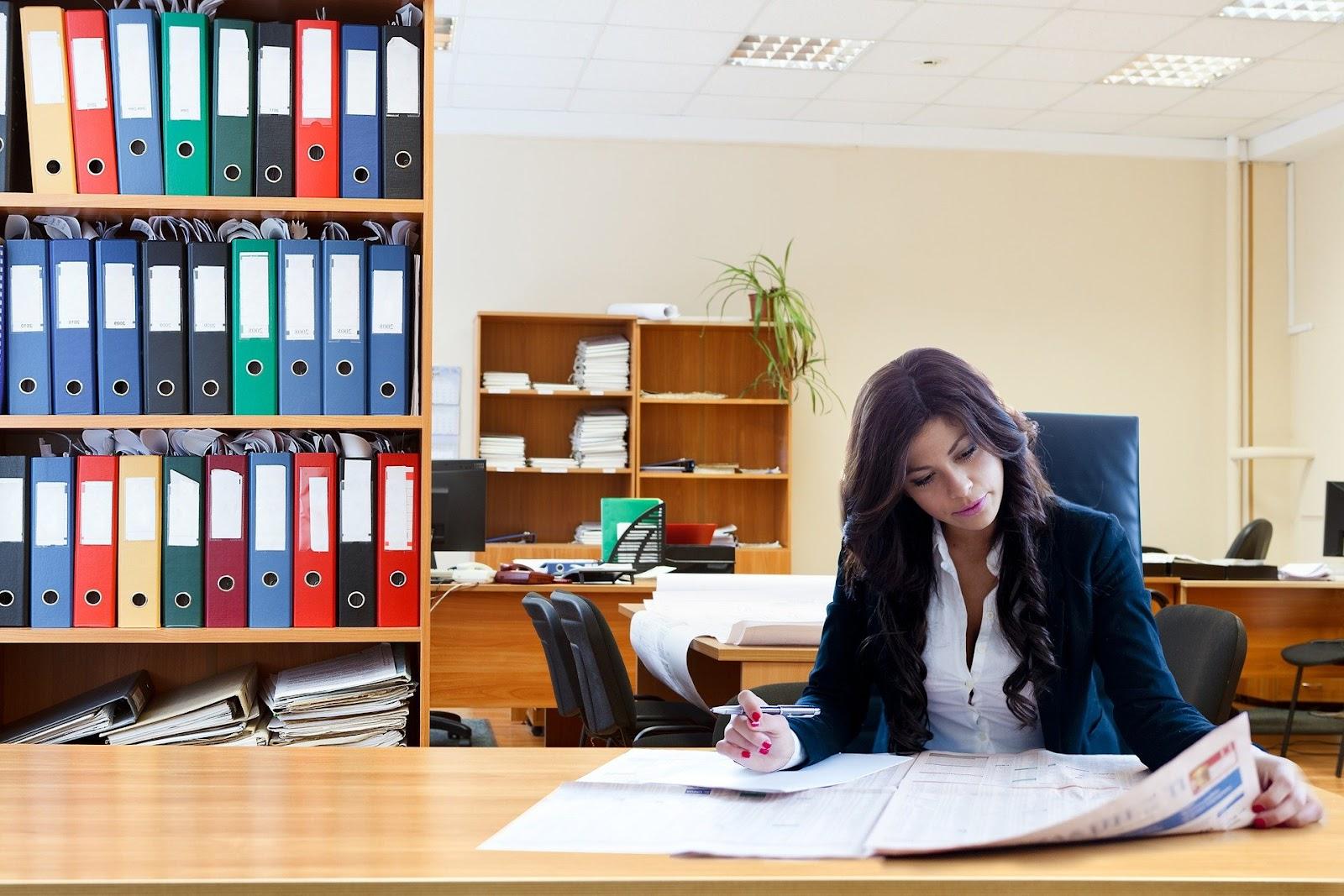 Uma mulher lendo um jornal em um escritório.