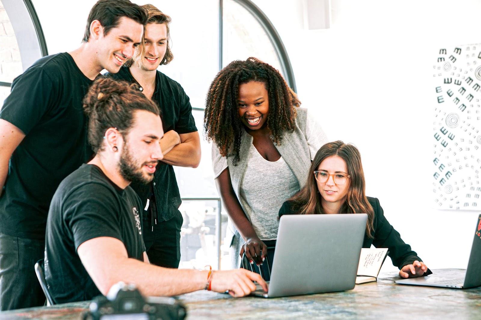 Pessoas em uma reunião com um computador organizando uma possível confraternização empresarial
