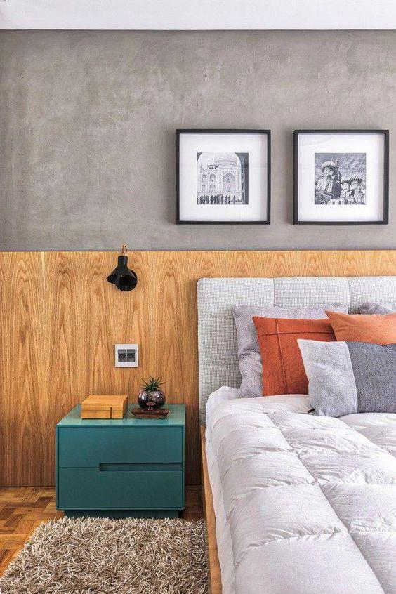 Quarto com técnica de meia parede de cimento queimado e inferior de madeira, cabeceira estofada cinza, criado mudo verde e piso de madeira.