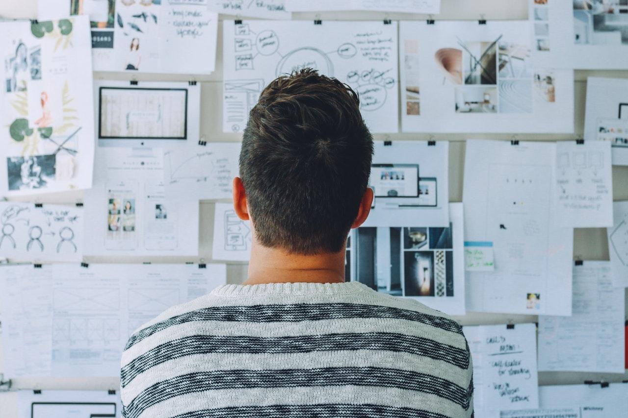 Mężczyzna spogląda na ścianę wypełnioną wieloma kartkami, i je analizuje.