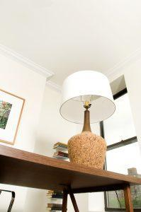 A natural stone table lamp with a white lamp-shade.
