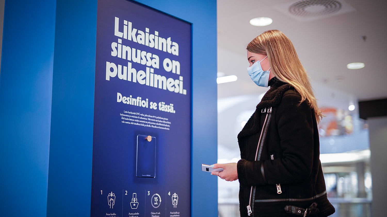 UV light terminal showing where to place one's phone to get sanitized (writing is in Finnish).