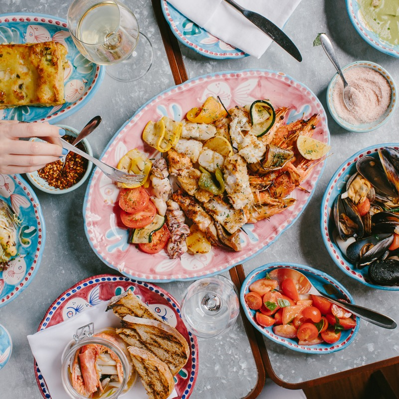 Overhead photo of vibrate seafood dishes from Osteria Marzia