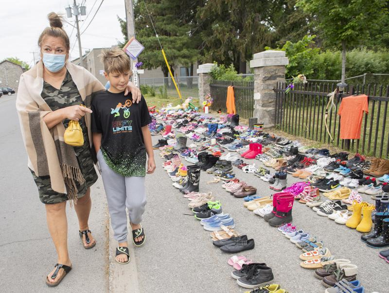 Lynn Karonhia-Beauvais and grandson Jamieson Kane walk past shoes representing the remains of 215 children outside St. Francis Xavier Church in Kahnawake, Quebec, Sunday, May 30, 2021. The remains of 215 children, some as young as 3 years old, have been found buried on the site of what was once Canada's largest Indigenous residential school — one of the institutions that held children taken from families across the nation. (Graham Hughes/The Canadian Press via AP)