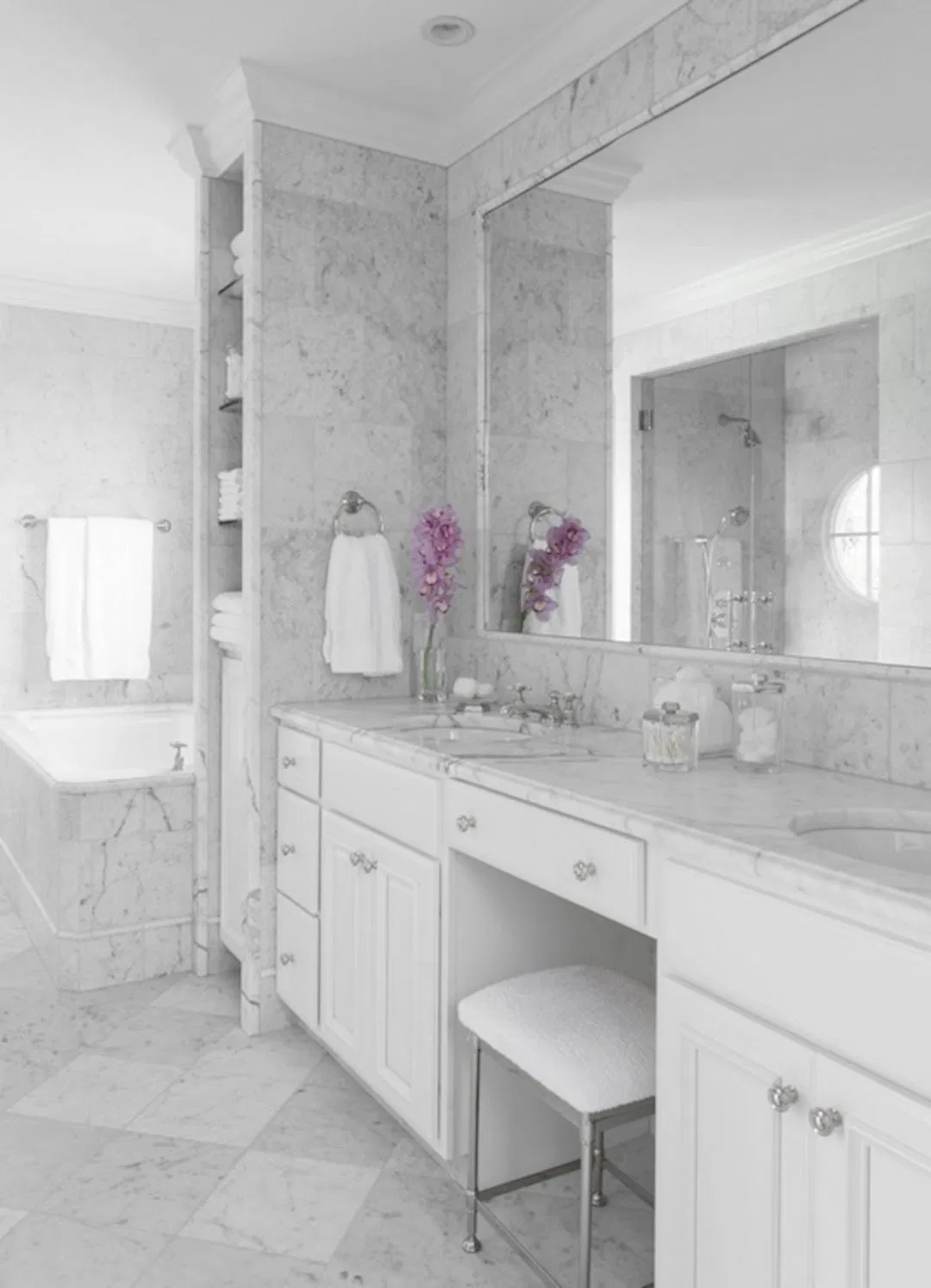 modern bathroom with marble wall finishes, marble tile floors, white cabinet vanity and small area for seating in front of mirror