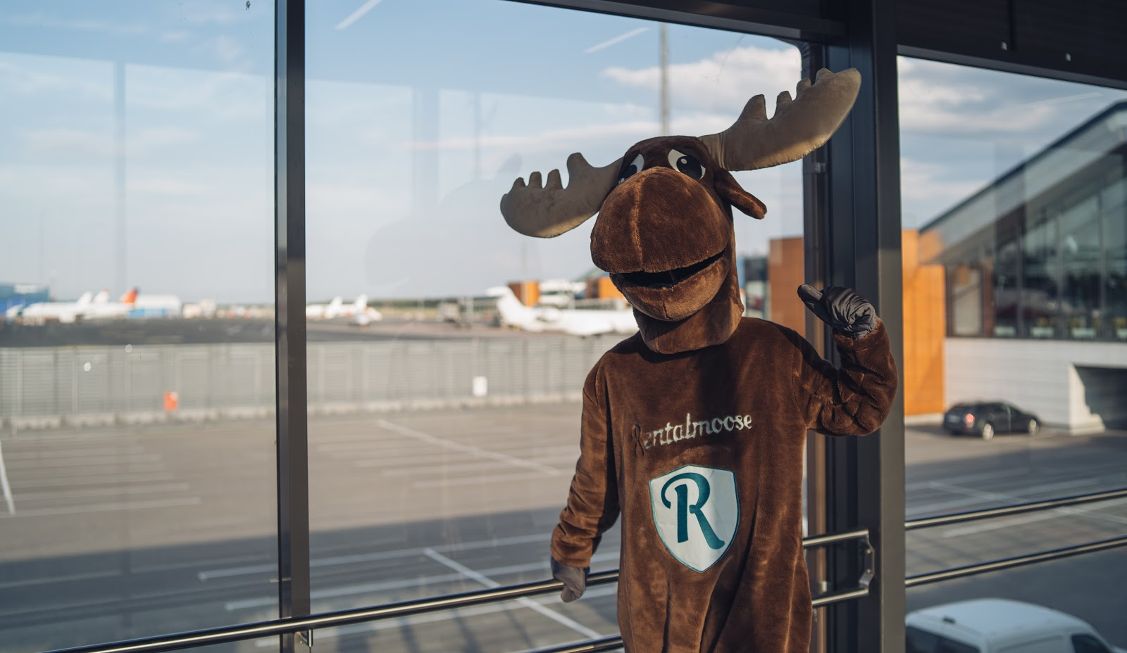 Rental Moose mascot posing at Tallinn airport, airplanes and runway behind glass panel. Rental Moose is a global car rental broker which will help you get the best deal on your next rental car.