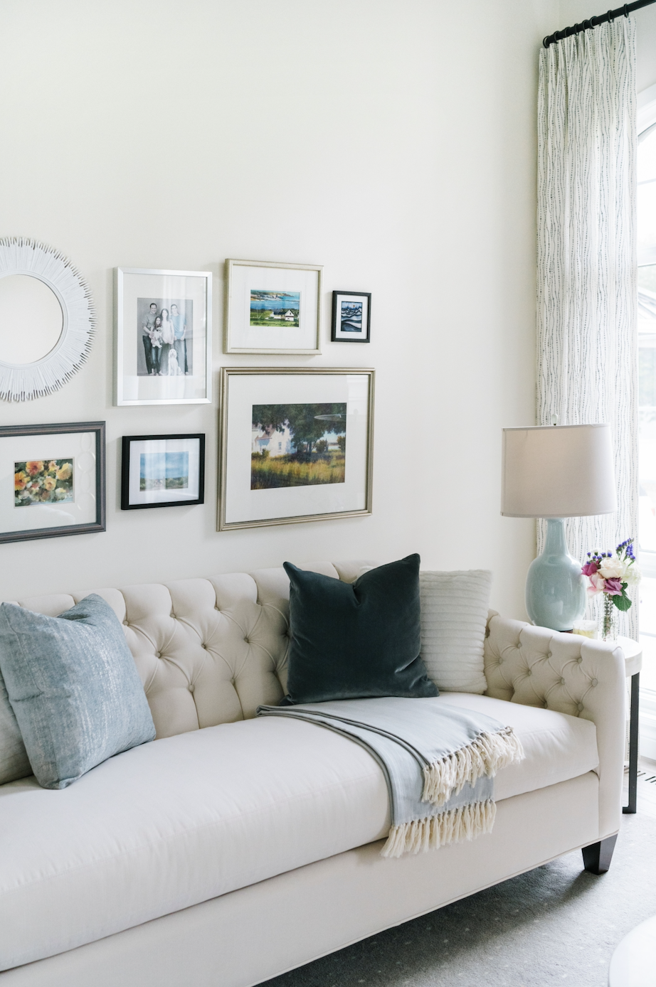 gallery wall white button tufted sofa blue pillows lamp silver gold brass frames calgary