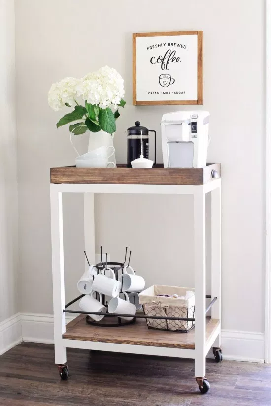 small rolling coffee cart made of wood on wheels, houses a white keurig and french press with matching white coffee mugs
