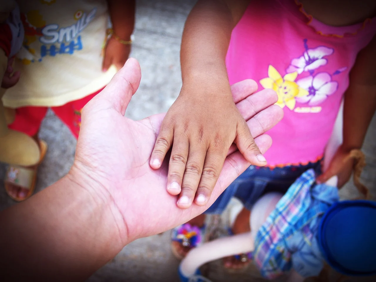 An adult holding hands with a small child.