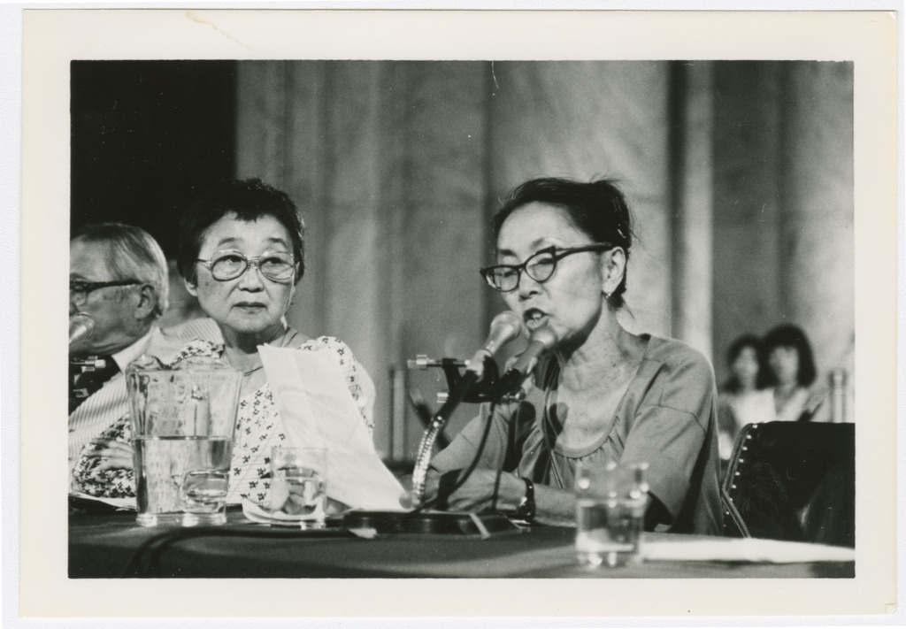 Yuri Kochiyama reading a written statement and speaking into a microphone. Next to her is another Japanese American woman looking on.