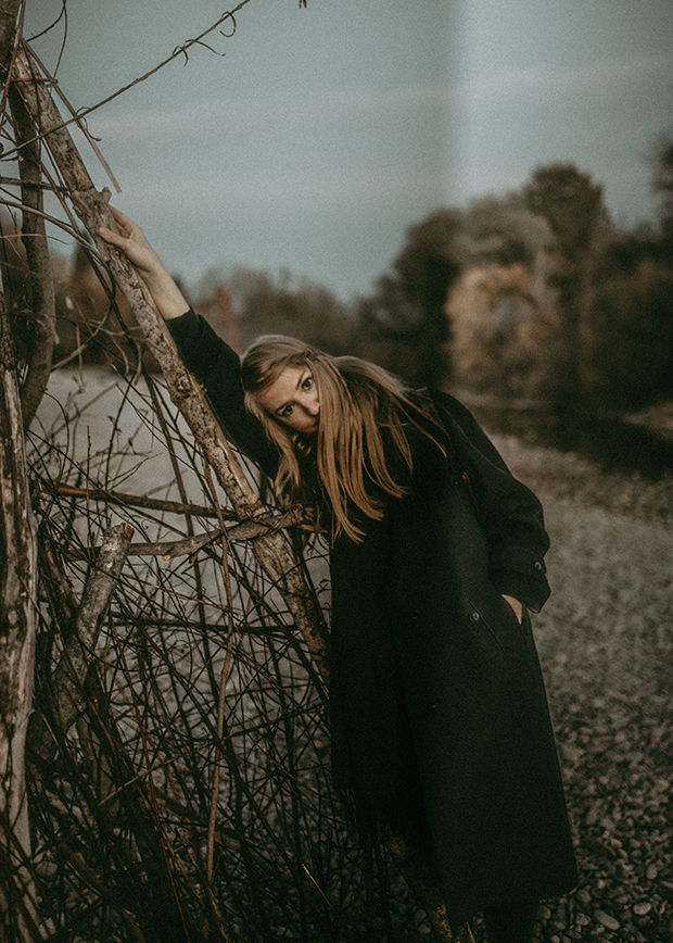 Darkly lit photo of a woman in a green coat with long hair leaned against a pile of sticks and turned toward the camera. The forest background is blurred behind her