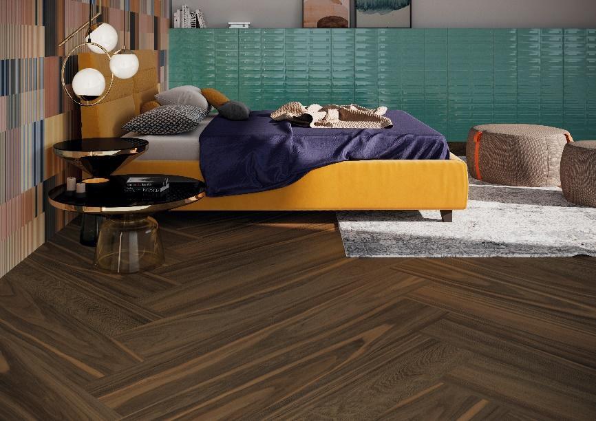 Quarto com piso de madeira escura, cama com cabeceira e estrutura amarela, revestimento no fundo da cabeceira com revestimento colorido e na lateral da cama parede com revestimento verde.