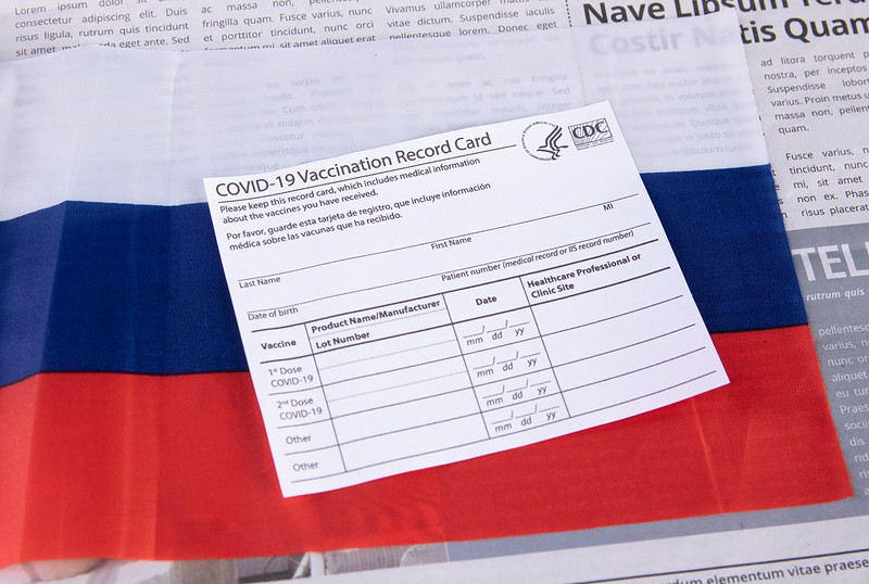 """U.S. Centers for Disease Control paper COVID-19 Vaccination Record Card laid atop a Russian flag in a stock photo. Russia's Foreign Minister Sergey Lavrov wore a mask with the words """"FCKNG QRNTN"""" during his March 22 trip to China. The Russian Foreign Ministry said """"Both the mask and the slogan suited the minister just right."""""""